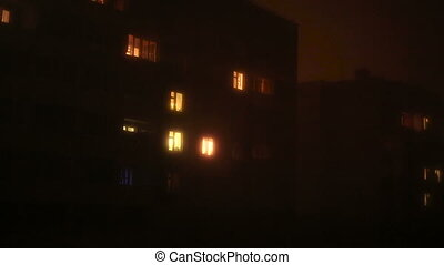 Light in the windows of a multistory building.