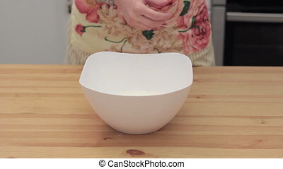 woman adds ghee in white bowl
