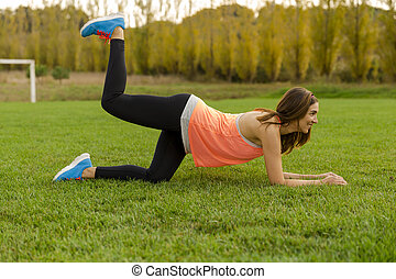 workout time - An attractive woman exercising outdoor on a...