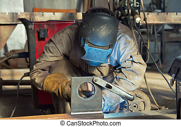 A welder fabricates steel structures using semi-automatic...