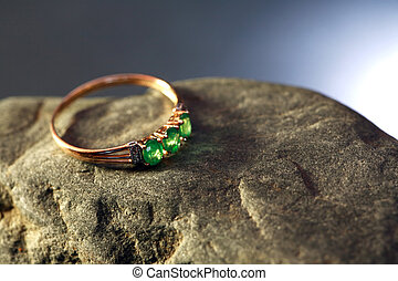 Gold And Emerald - Gold ring with emerald on gray stone...