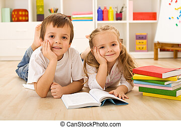 Happy kids with books laying on the floor