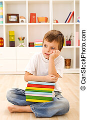 Boy with lots of books thinking hard sitting on the floor