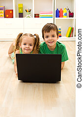 Kids with laptop laying on the floor at home