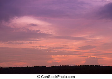 Silhouette of sunset over dark black mountain (for...