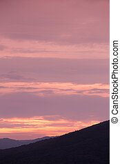Silhouette of sunset over dark black mountain for background...