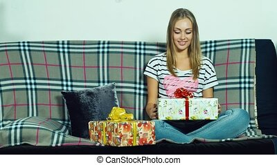 Attractive woman sitting on the couch and unpacks a gift, Concen: New Year gifts, Christmas, a birthday gift