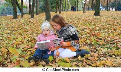 little sisters read the book in the autumn park