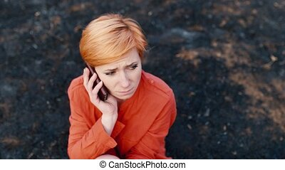 The sad woman sitting on the ground with the phone