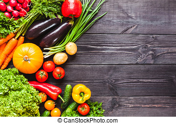 Background of wooden black planks with fresh vegetables. -...