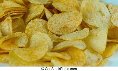 Potato chips are rotated in front of camera