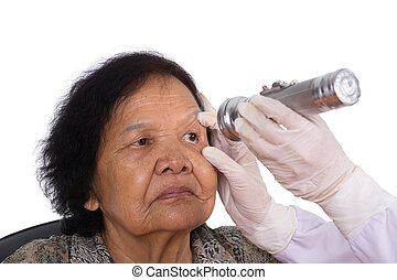 Neurologist testing reflexes of the eye of young woman on...