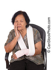 senior woman with an injured arm wrapped in an Elastic...