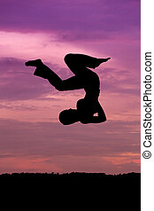 Silhouette of woman jumping at sunset