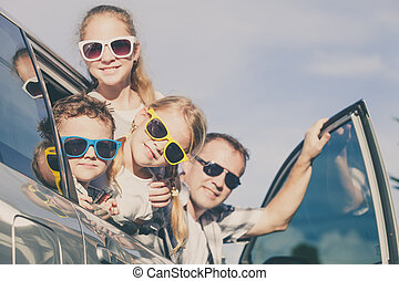 Happy family getting ready for road trip on a sunny day....