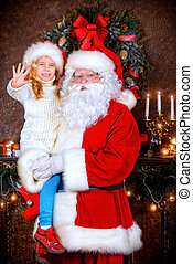 christmastime - Santa Claus holds on hands happy little girl...