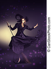 flying on a broom - Portrait of a gorgeous brunette witch...