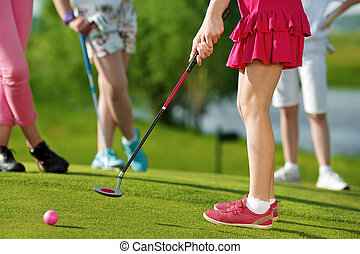 Kids playing golf - Legs of kids playing golf and hitting by...