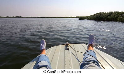 Legs of Girl on Bow of Motorboat Floating on Water Surface...