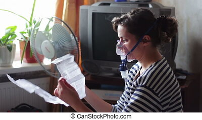 Woman wears a mask for inhalation, and conducts the...