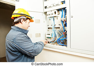 Electrician installing energy saving meter - electrician...