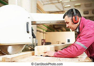 carpentry worker cutting wood cross beam
