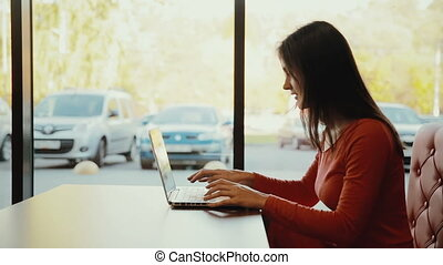 woman typing on laptop, smiling at cafe. profile