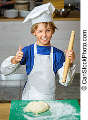 Funny happy chef boy cooking at restaurant kitchen and...