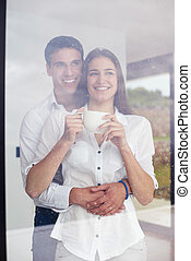 relaxet young couple drink first morning coffee over big...