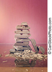 Stack of chocolate on reflective glass against red...