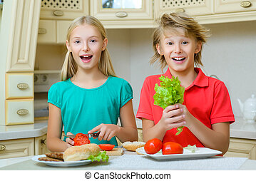 smiling boy holding salad standing next to girl who cuts the tomato in kitchen