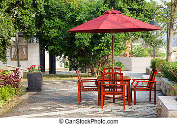 Summer Patio with tables and wooden chairs under umbrella in...