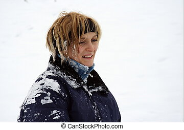 Winter fun - Woman covered with snow from snowballs.
