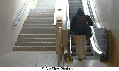 Train Station Escalators - Adult man steping on to the...
