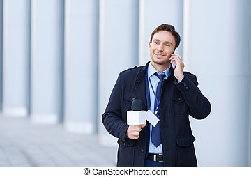 Smiling newsman is speaking on the phone. - Getting...