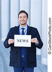 Smiling journalist holds a sheet of paper. - News time....