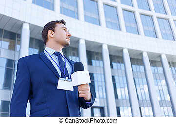Journalist with microphone stands near the office. - Get...