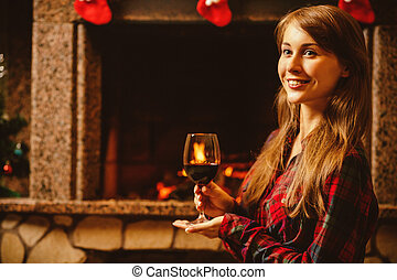 Woman with a glass of wine by the fireplace. Young...