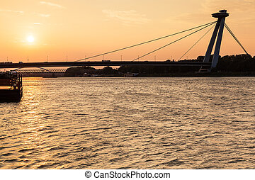 SNP bridge across Danube river at yellow dawn - travel to...
