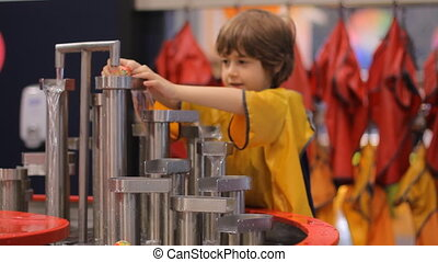 Boy plays with water at children museum of science