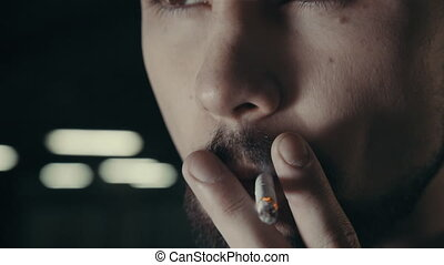young handsome bearded man smoking cigarette - young...