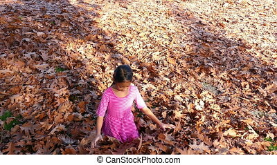 Girl Throws Autumn Leaves In Air - A cute little 9 year old...