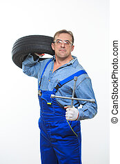 adult male mechanic with a wrench and tire in the goggles