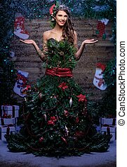 Woman in christmas tree dress standing under snow