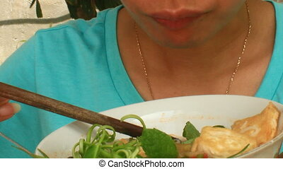 woman eating noodles and tofu, vegetables
