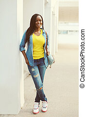 Beautiful happy smiling african woman wearing a jeans shirt...
