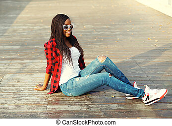 Fashion pretty young african woman sitting in city park, wearing a red checkered shirt and sunglasses