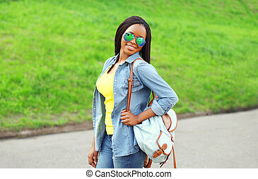 Portrait happy smiling african woman wearing a sunglasses, jeans shirt and backpack in city park