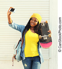 Beautiful smiling african woman with skateboard taking self-portrait picture on smartphone in city, wearing a colorful yellow clothes