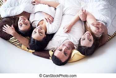 handsome man in bed with three beautiful woman - young macho...